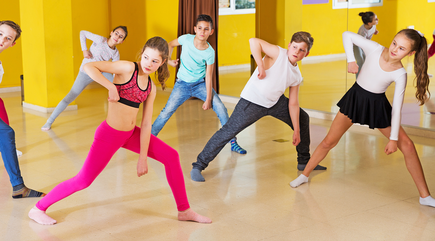 Teenage boys and girls practicing dance, stretching with female trainer in dance hall