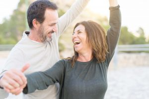 Romantic couple smiling and dancing on a sunny day