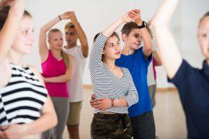 Group of happy french teen dancing salsa in dance studio